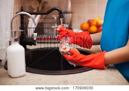 Washing the dishes after a meal - child hands scrubbing a glass and rinsing under the water jet, shallow depth