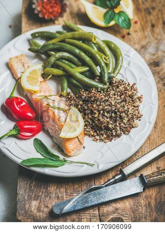 Healthy protein rich dinner plate. Oven roasted salmon fillet with multicolored quinoa, chilli pepper and poached green beans on rustic wooden board. Clean eating, weight loss, dieting food concept