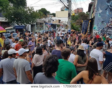 Sao Paulo, Brazil - February 11, 2017: Street carnival at Beco do Batman (Batman's alley) in the Vila Madalena neighborhood in Sao Paulo. Revelers take part in a street block parade.