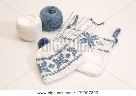 Knitting Clothes For The Newborn On A White Background. Needles And Yarn For Knitting.