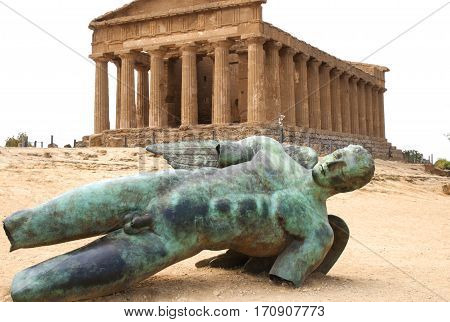 Fallen bronze statue of Icarus in front of the temple of Concordian in the valley of temples, Agrigento, sicily, Italy
