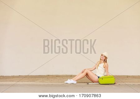 Travel adventure teenage journey concept. Woman wearing denim shorts white top and sun hat suitcase holding suitcase on wheels hitchhiking sitting and relaxing during trip
