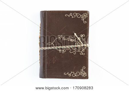 A small leather journal on a white background.