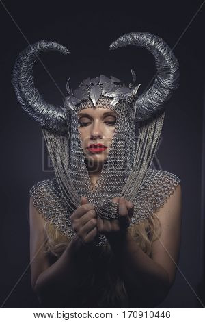 Legend, Viking goddess, beautiful young blond woman with horned helmet made of iron. Fantasy image and stories