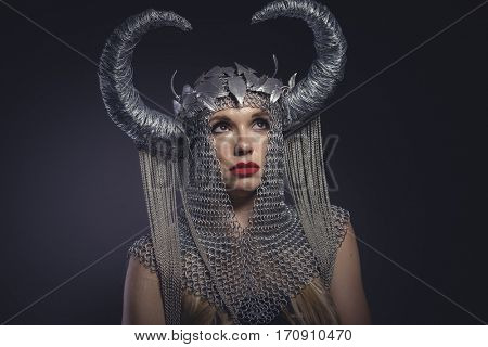 Cosplay, Viking goddess, beautiful young blond woman with horned helmet made of iron. Fantasy image and stories