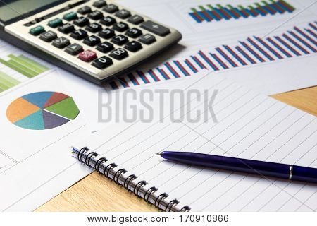 Blank note book with financial graph calculator and pen background