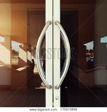 Chrome door handle and glass of aluminium door outside building.
