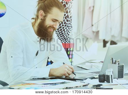 modern fashion designers drawings in the creative studio working with a graphics tablet