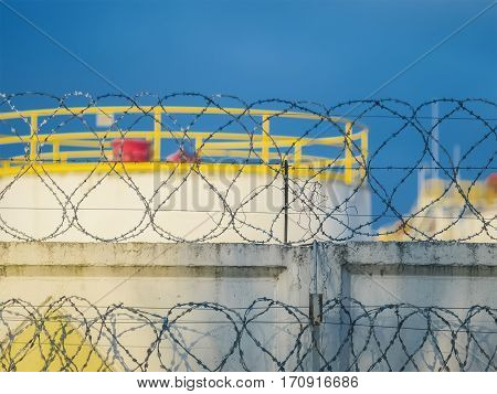 The barbed wire on the fence near the oil tanks