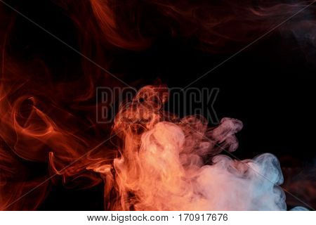 Abstract smoke sepia. Personal vaporizers fragrant steam. The concept of alternative non-nicotine smoking. Orange turquise smoke on a black background. E-cigarette. Evaporator. Taking Close-up. Vaping.