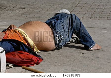 A drunk with a swollen stomach lays sleeping on the street