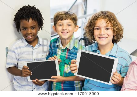 Portrait of smiling students holding digital tablet in classroom at elementary school