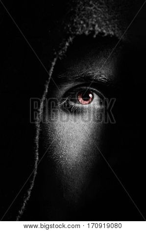 Eye of spooky man in hood