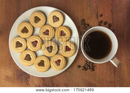 A coffee mug, butter cookies with heart-shaped chocolate filling, and coffee beans, shot from above on a dark wooden table