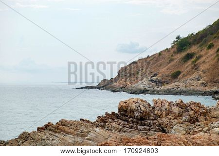 Rock cliff with view of the sea coastline at Khao Laem Ya Mu Ko Samet National Park in Thailand.