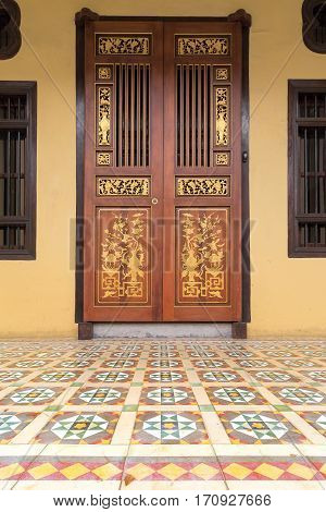 Ornate Doors of Peranakan Style exterior with Chinese wood carvings and colorful tiles entrance