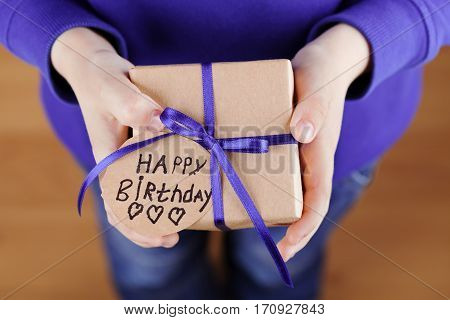 Childrens hands holding a gift or present in kraft paper and tag with note Happy Birthday. Holiday concept, top view.