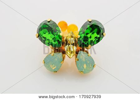 Closeup studio shot of crystal butterfly ring with natural stone beads. Yellow and green. Copy space.