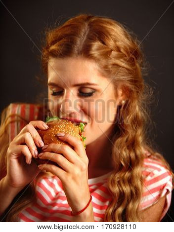 Woman eating fast food . Girl enjoying delicious hamburger, eyes closed. Pretty female student with sandwich on a black background.