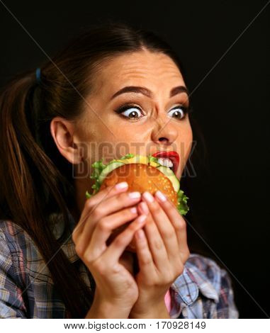 Woman eating hamburger. Girl wants to eat burger. Student consume fast food. Portrait of person with good appetite have greedily dinner delicious sandwich on a black background.
