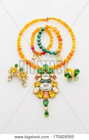 Closeup studio shot of jewelry set of necklace, bracelets, ring and earrings with natural stone beads and crystals. Yellow, orange and green. Copy space.