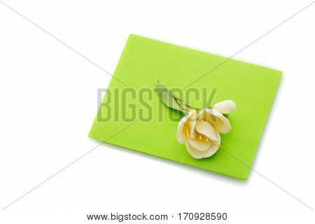 Closeup shot of small green envelope decorated with art clay tulip. Handmade paper work. Copy space. Isolated over white background. Square composition.