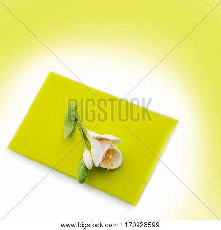 Closeup shot of small green envelope decorated with art clay tulip. Handmade paper work. Copy space. Over green background background. Square composition.
