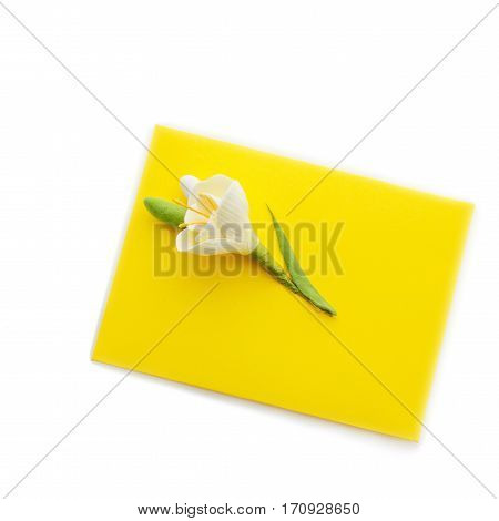 Closeup shot of small yellow envelope decorated with art clay tulip. Handmade paper work. Copy space. Isolated over white background. Square composition.