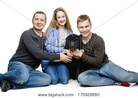 Family portrait. Father with teen age son and daughter sitting on floor hugging black shar pei dog. Isolated on white background. Copy space.
