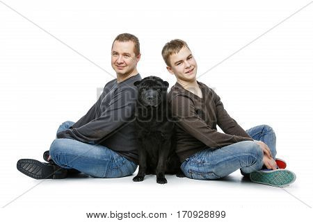 Family portrait. Father with teen age son sitting on floor with black shar pei dog. Isolated on white background. Copy space.