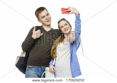 Beautiful teen age boy and girl in casual clothes taking selfie photo using mobile phone. School children isolated on white background. Copy space.