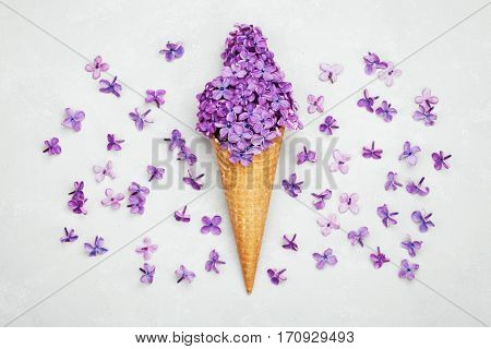 Ice cream of lilac flowers in waffle cone on light gray background from above. Beautiful floral arrangement, vintage color. Flat lay styling.