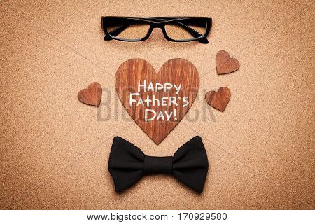 Spectacles, bowtie and wooden heart with note Happy Fathers Day. Cork board background top view, flat lay.