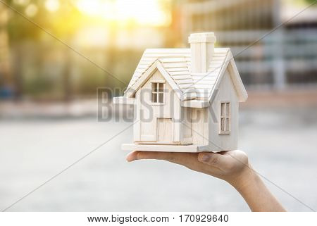 close up of hands holding house or home model,small wood house in hands