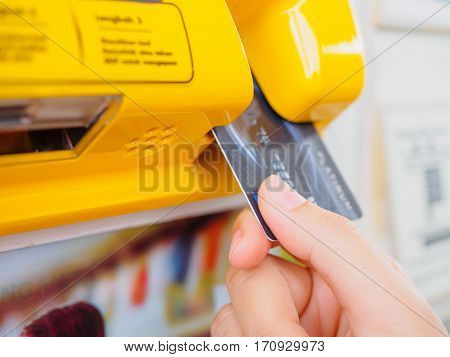 Hand is holding the credit card and insert to the machine