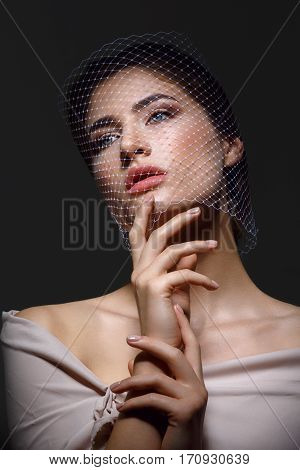 Portrait of beautiful young woman with natural makeup. Face covered in veil net. Hands with beige nude manicure. Studio shot on black background. Copy space.