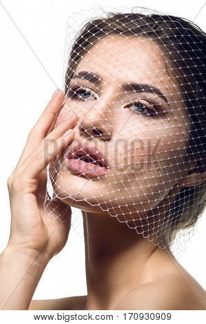 Portret of beautiful young woman with natural makeup. Face covered in veil net. Hands with beige nude manicure. Studio shot. Isolated on white background. Copy space.