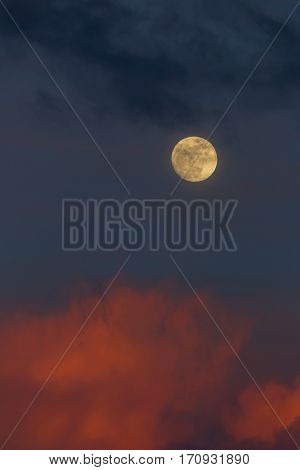 Moonrise in the East during sunset with pink clouds and blue sky