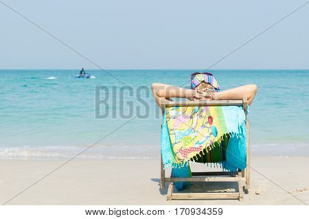 Woman sitting on the seat, sunbathing on the beach in Chonburi, Thailand.
