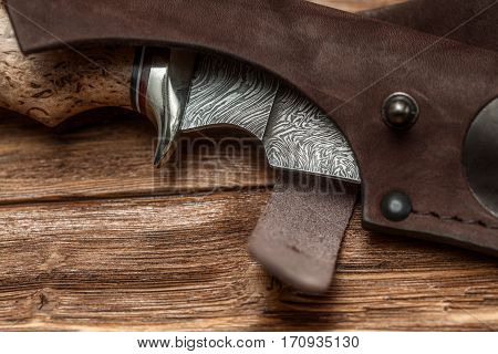 Hunting damascus steel knife handmade in sheath on a brown wooden background closeup