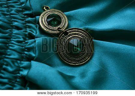 beautiful female decoration with emerald stone on an emerald background