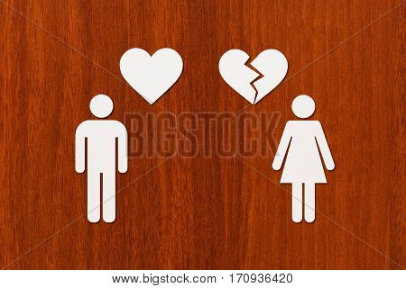Paper man with heart and woman with broken one on wooden background. Unrequited love or divorce concept. Abstract conceptual image