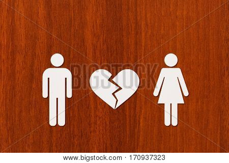 Paper man and woman with broken heart on wooden background. Abstract conceptual image