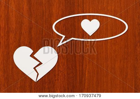 Paper broken heart is thinking about love on wooden background. Abstract conceptual image