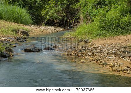 Rocky little stream with lush green vegetation in tropical Vietnam.