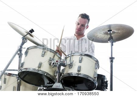 white drummer behind drum set wears white shirt and plays the drums in studio with concentration