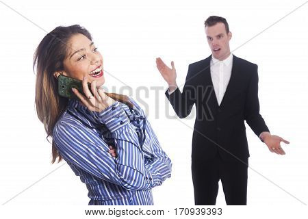 young corporate woman talks into mobile phone while man in black suit looks not amused