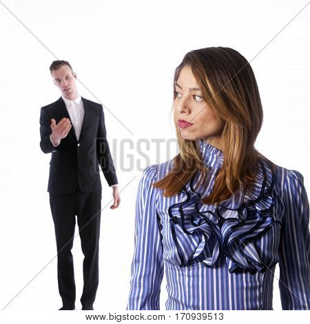 female subordinate worries anxiously while male boss beckons in background with adamant gesture