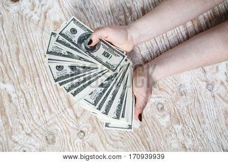 Dollar banknotes in hands. Woman hands counting dollar banknotes on light wooden background.