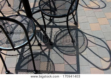 Several black mesh metallic bistro chairs, casting shadows outside on tiled courtyard